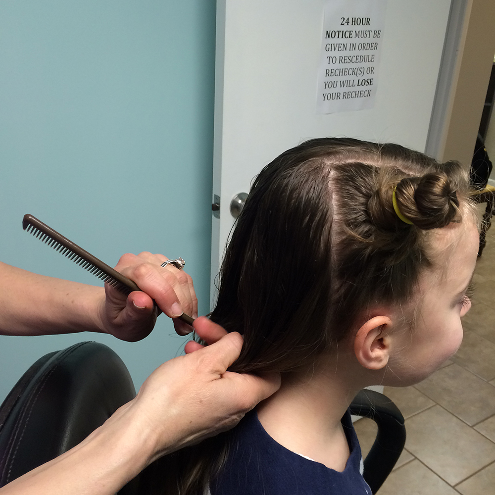 child having lice removed